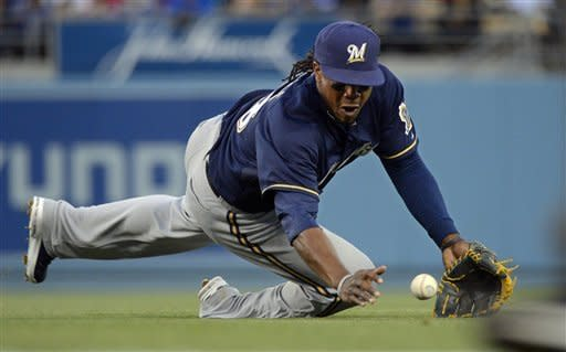 Milwaukee Brewers second baseman Rickie Weeks dives for a ball hit for a single by Los Angeles Dodgers' Clayton Kershaw during the inning second of their baseball game, Wednesday, May 30, 2012, in Los Angeles. (AP Photo/Mark J. Terrill)