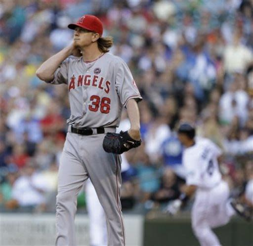 Los Angeles Angels starting pitcher Jered Weaver, left, watches the path of the ball as Seattle Mariners' Raul Ibanez heads to second base on a double in the first inning of a baseball game Saturday, July 13, 2013, in Seattle. (AP Photo/Elaine Thompson)