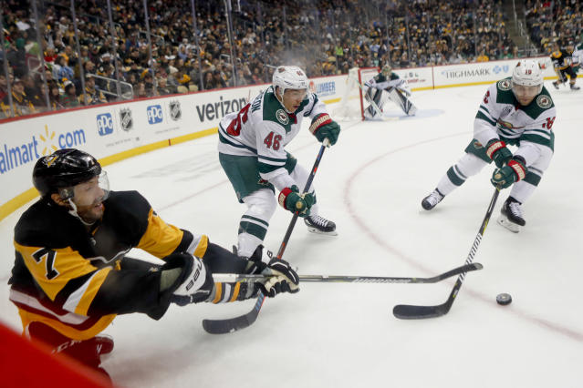 Pittsburgh Penguins' Matt Cullen (7) tries to control the puck as Minnesota Wild's Jared Spurgeon (46) and Jason Zucker, right, defend during the second period of an NHL hockey game Thursday, Dec. 20, 2018, in Pittsburgh. (AP Photo/Keith Srakocic)