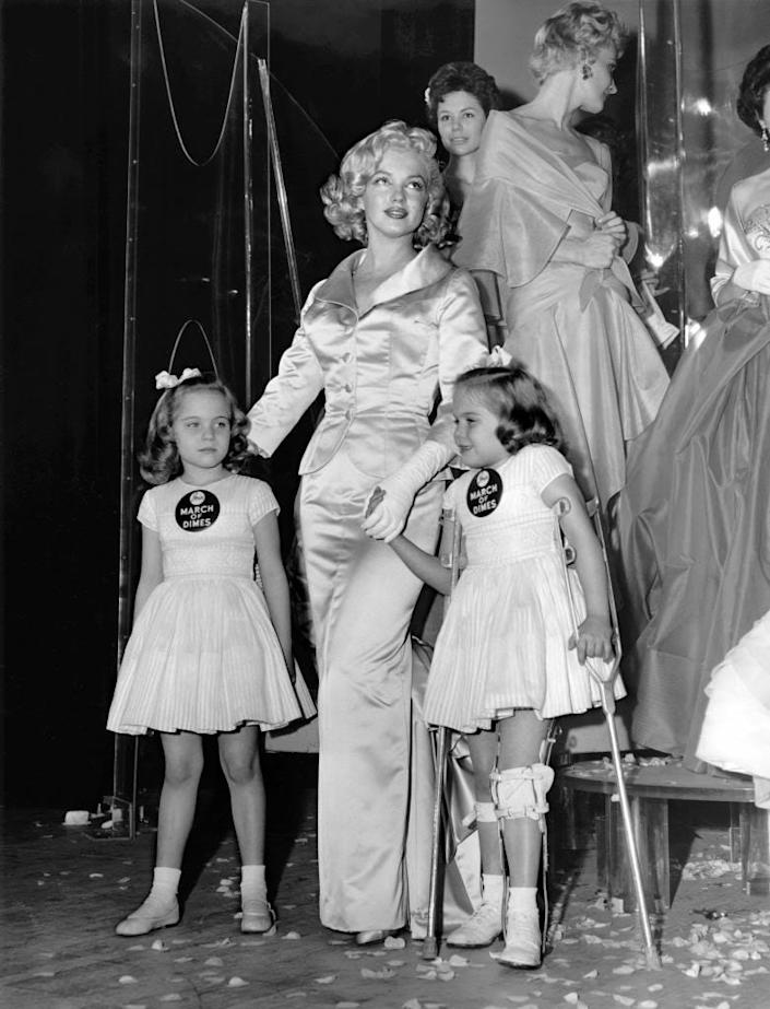 Actress Marilyn Monroe with March of Dimes figureheads Linda and Sandra Solomon from 1958 and the 14th annual March of Dimes fashion show in 1958.