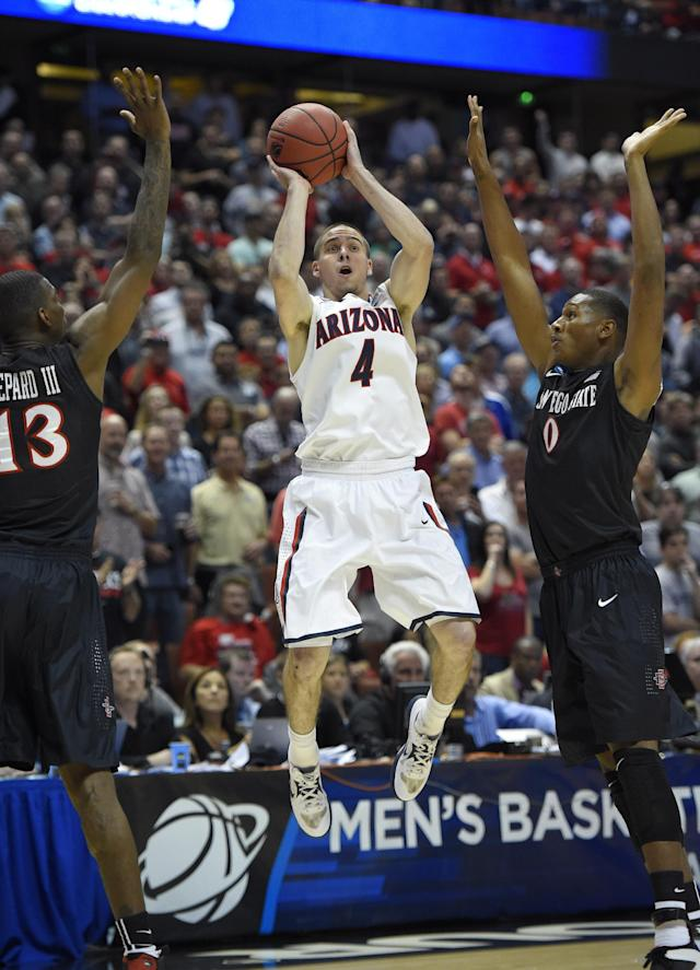 Arizona guard T.J. McConnell (4) (4) shoots over San Diego State forward Winston Shepard (13) and San Diego State forward Skylar Spencer (0) during the first half in a regional semifinal NCAA college basketball tournament game, Thursday, March 27, 2014, in Anaheim, Calif. (AP Photo/Mark J. Terrill)