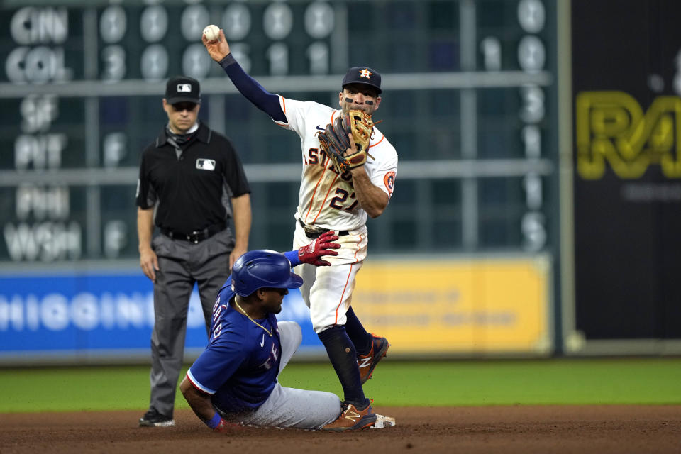 Houston Astros second baseman Jose Altuve (27) throws first for a double play as Texas Rangers' Andy Ibanez slides into second base during the 10th inning of a baseball game Thursday, May 13, 2021, in Houston. Ibanez was out at second and Khris Davis was out at first on the double play. (AP Photo/David J. Phillip)