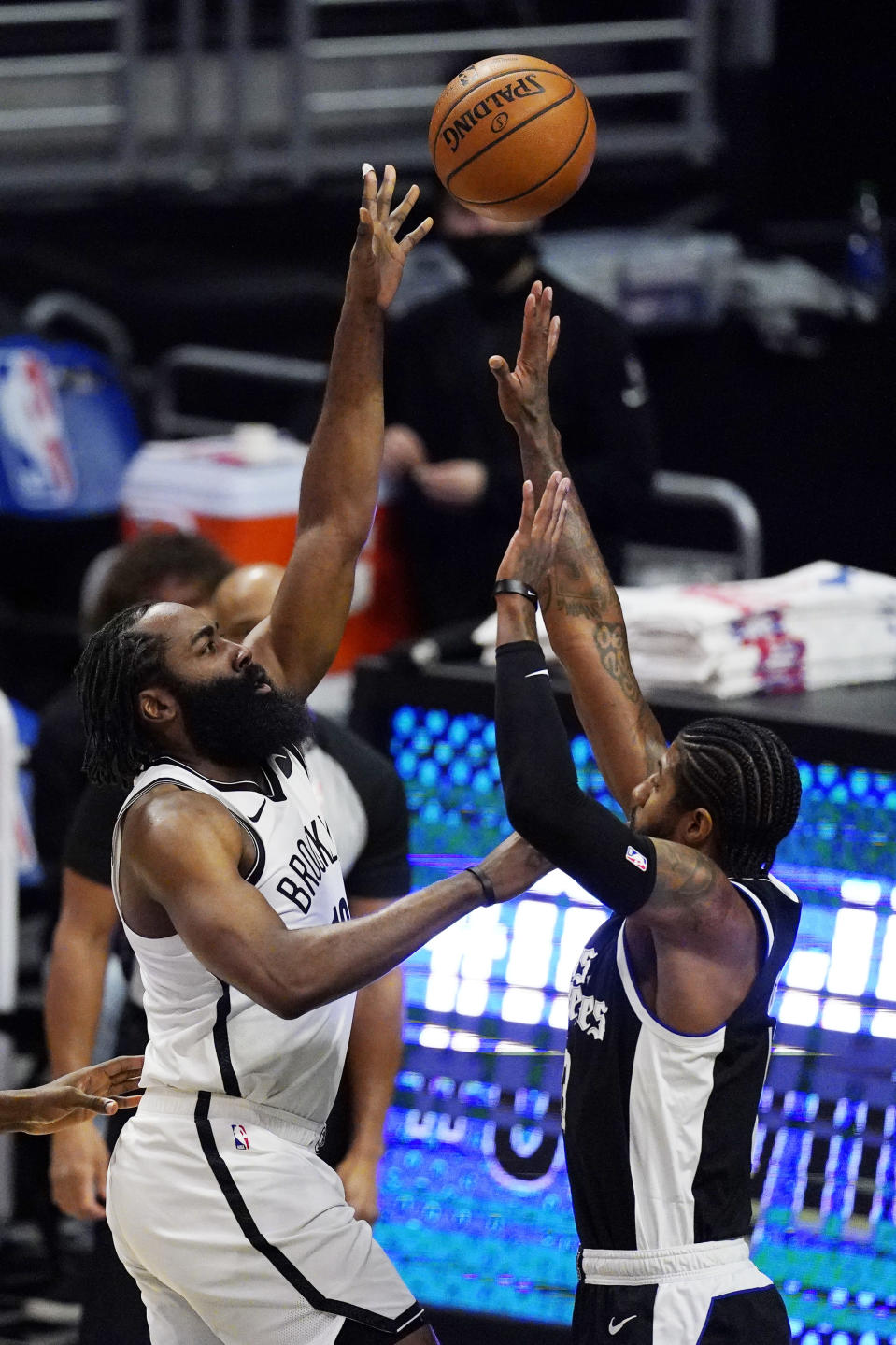 Brooklyn Nets guard James Harden, left, shoots as Los Angeles Clippers guard Paul George defends during the first half of an NBA basketball game Sunday, Feb. 21, 2021, in Los Angeles. (AP Photo/Mark J. Terrill)