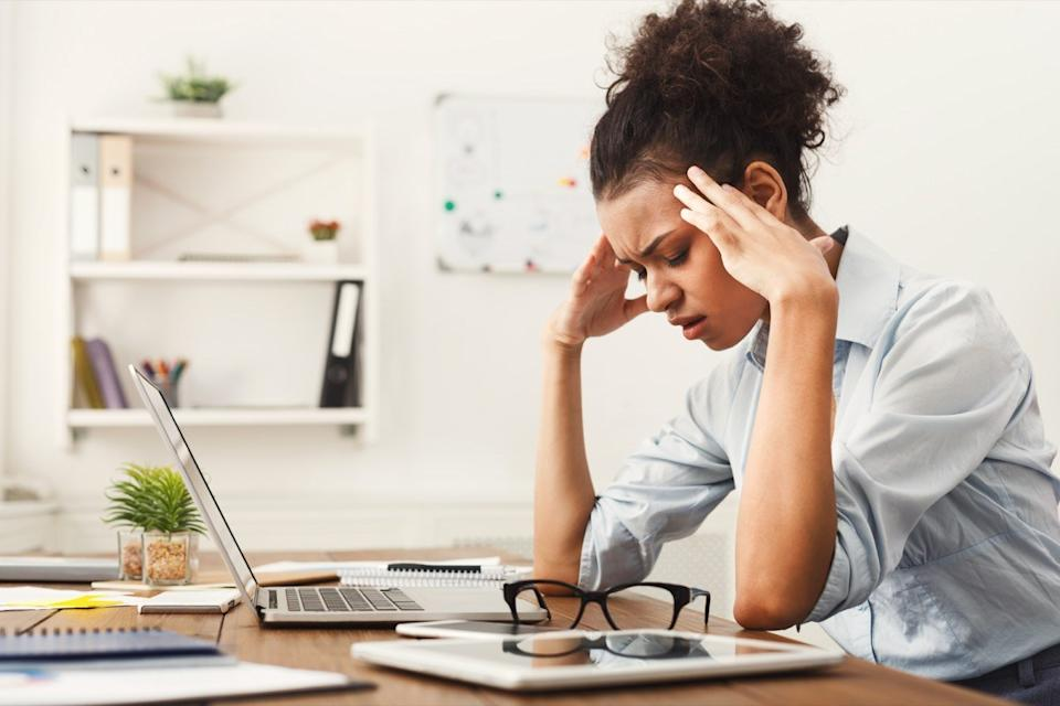 Woman with a headache while she is working