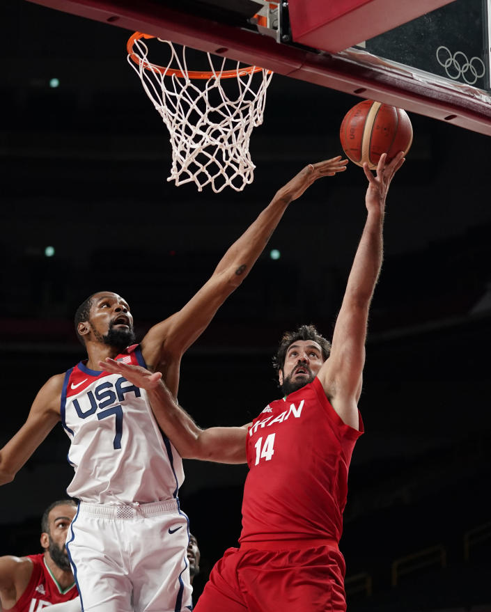 Iran's Mohammadsamad Nik Khahbahrami (14), right, scores ahead of United States' Kevin Durant (7) during men's basketball preliminary round game at the 2020 Summer Olympics, Wednesday, July 28, 2021, in Saitama, Japan. (AP Photo/Charlie Neibergall)