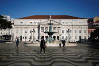 People walk by Rossio square on the first day of the second national lockdown due to coronavirus disease (COVID-19) pandemic in Lisbon