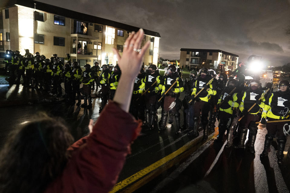 A demonstrator raises their hand while facing off against a perimeter of police as they defy an order to disperse during a protest against the police shooting of Daunte Wright, late Monday, April 12, 2021, in Brooklyn Center, Minn. (AP Photo/John Minchillo)