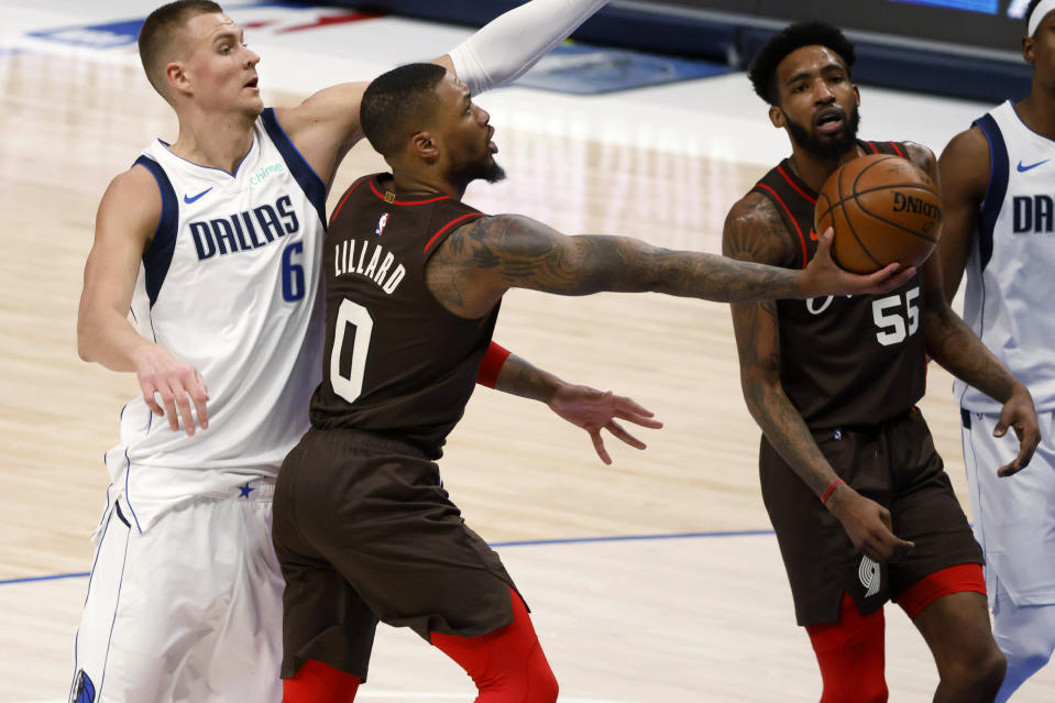 Portland Trail Blazers guard Damian Lillard (0) goes for a layup in front of Dallas Mavericks center Kristaps Porzingis (6) during the second half of an NBA basketball game in Dallas, Sunday, Feb. 14, 2021. (AP Photo/Michael Ainsworth)