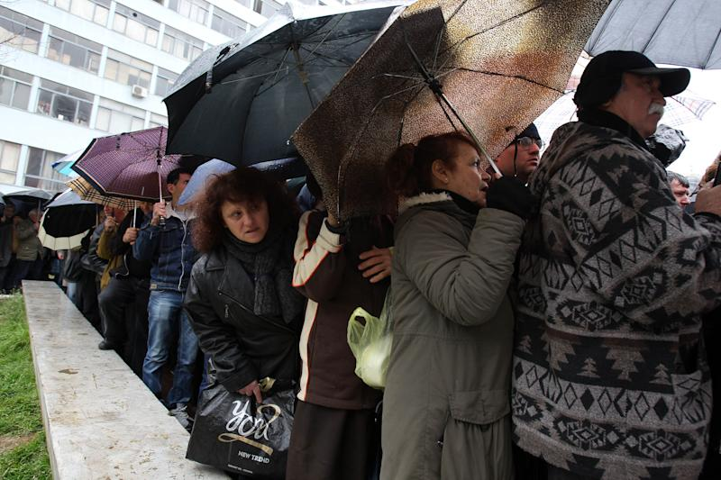 "People line up for free meat lunches under a rainfall in Athens on Thursday, March 7, 2013. It's called ""Barbecue Thursday"" _ a raucous pre-Easter celebration for meat lovers. But this year's Tsiknopempti festivities, a fixture of the Carnival season, coincided with the Greek Statistical Authority announced unemployment in Greece has dipped marginally to 26.4 percent, according to data for December. (AP Photo/Thanassis Stavrakis)"