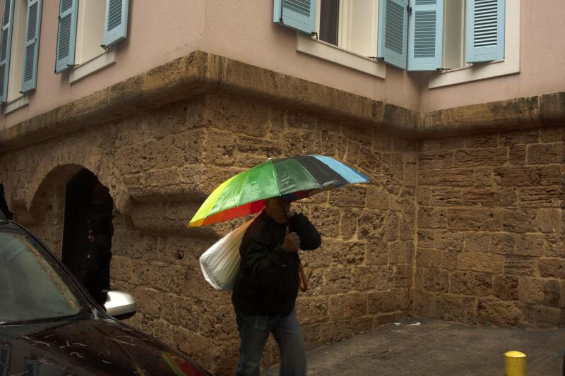 A man walks with an umbrella past the house of ex-Nissan chief Carlos Ghosn in Beirut, Lebanon, Friday, Jan. 3, 2020. The former Nissan Motor Co. Chairman fled Japan this week while awaiting trial on financial misconduct charges and appeared in Lebanon. (AP Photo/Maya Alleruzzo)
