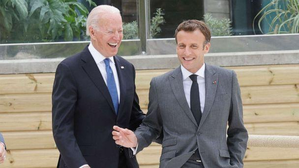 PHOTO: U.S. President Joe Biden and French President Emmanuel Macron share a light moment before the family photo at the start of the G-7 summit in Cornwall, England on June 11, 2021. (Ludovic Marin/AFP via Getty Images)