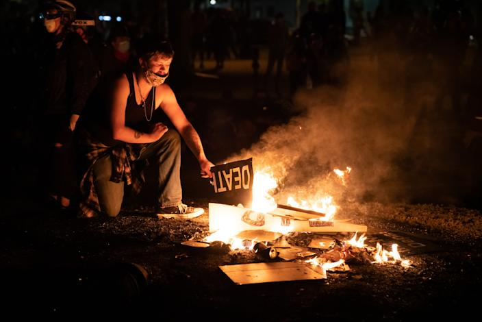 A protester burns signs during a break in confrontations between federal agents and a large crowd at the federal courthouse in Portland, Ore., in the early hours of July 26, 2020.