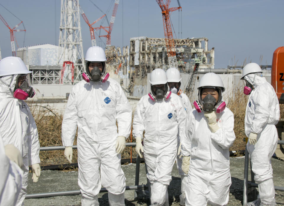 Member of the media, wearing protective suits and masks, visit the Unit 3 and Unit 4 reactor buildings of Tokyo Electric Power Co.,'s tsunami-crippled Fukushima Dai-ichi nuclear power station, during a press tour escorted by TEPCO officials, in Okuma, Fukushima prefecture, northeastern Japan,  Tuesday, Feb. 28, 2012.   The Japanese government withheld information about the full danger of last year's nuclear disaster in the nuclear plant from its own people and from the United States, putting U.S.-Japan relations at risk in the first days after the accident, according to an independent report released Tuesday. (AP Photo/Kimimasa Mayama, Pool)