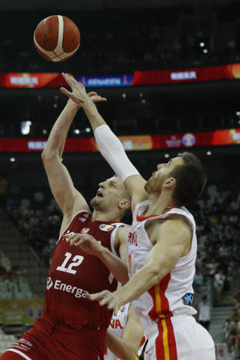 Adam Waczynski of Poland tries to put a shot over Victor Claver of Spain during their quarterfinals match for the FIBA Basketball World Cup at the Shanghai Oriental Sports Center in Shanghai, Tuesday, Sept. 10, 2019. (AP Photo/Andy Wong)
