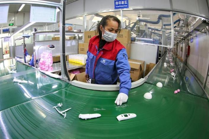The Chinese government has responded by mobilising the entire country to increase production of masks and suits (AFP Photo/STR)