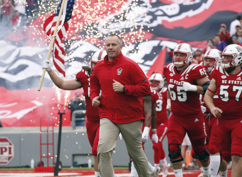 North Carolina State head coach Dave Doeren leads the team onto the field for an NCAA college football game against East Carolina in Raleigh, N.C., Saturday, Dec. 1, 2018. (AP Photo/Chris Seward)