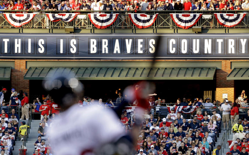 FILE - In this April 1, 2013 file photo, fans watch from the outfield as Atlanta Braves' Jason Heyward swings at a pitch in the first inning of an opening day baseball game against the Philadelphia Phillies, in Atlanta. The Atlanta Braves are leaving Turner Field and moving into a new 42,000-seat, $672 million stadium complex in Cobb County in 2017. Braves executives John Schuerholz, Mike Plant and Derek Schiller said Monday, Nov. 11, 2013, that the team decided not to seek another 20-year lease at Turner Field and began talks with the Cobb Marietta Coliseum and Exhibit Hall Authority in July.(AP Photo/David Goldman, File)