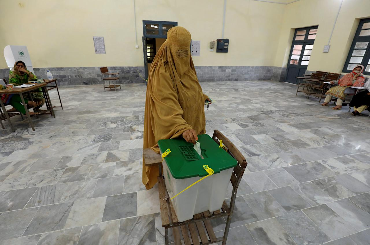 FILE PHOTO: A woman, clad in burqa, casts her ballot at a polling station during general election in Peshawar, Pakistan July 25, 2018. REUTERS/Fayaz Aziz/File Photo