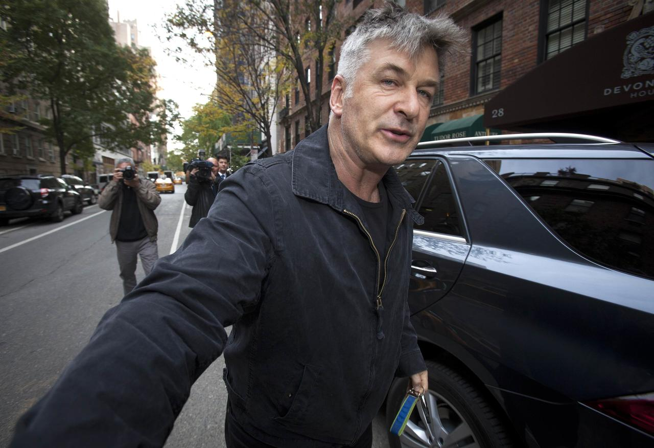 Actor Alec Baldwin shoves a photographer and tells him to move out of his way after he arrived in his SUV at the building where he lives in New York November 15, 2013. Baldwin assaulted a reporter earlier in the day, according to local media. In the earlier incident, he smacked a mobile phone from the reporter�s hands and shoved him against a car. REUTERS/Carlo Allegri (UNITED STATES - Tags: TPX IMAGES OF THE DAY ENTERTAINMENT)
