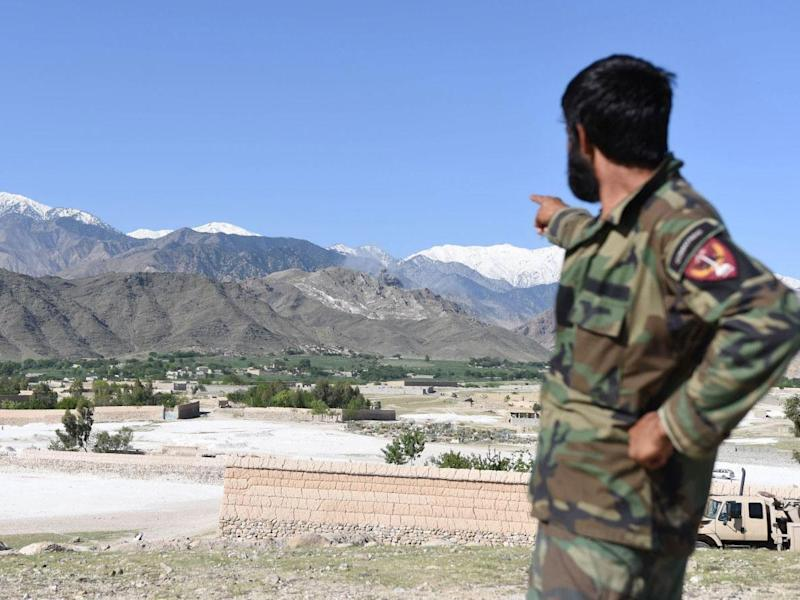 A member of Afghan security points to the mountainous area where the US dropped a MOAB bomb targeting Isis caves in Nangarhar province, Afghanistan (EPA/GHULAMULLAH HABIBI)
