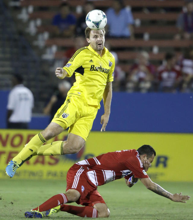 Columbus Crew defender Chad Marshall, top, heads the ball over FC Dallas forward Blas Perez during the first half of an MLS soccer game Sunday, Sept. 29, 2013, in Frisco, Texas. (AP Photo/LM Otero)