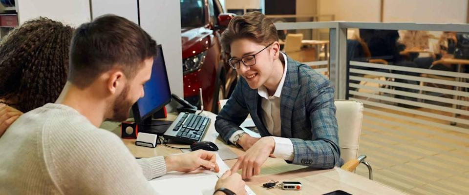 smiling handsome shop assistant explaing the features of luxury car, close up photo. dealer asking family to sign a document. close up photo