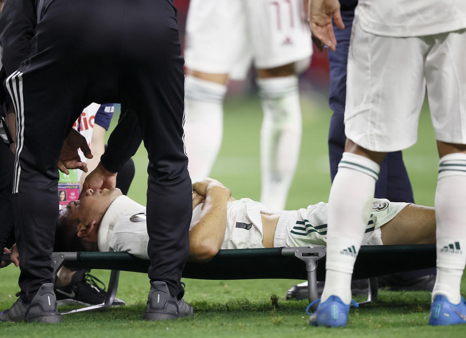 ARLINGTON, TEXAS - JULY 10: (EDITORS NOTE: Image contains graphic content.) Medical officials attend to Hirving Lozano #22 of Mexico after being injured in the first half against Trinidad and Tobago in the 2021 CONCACAF Gold Cup Group A Match at AT&T Stadium on July 10, 2021 in Arlington, Texas. (Photo by Tom Pennington/Getty Images)