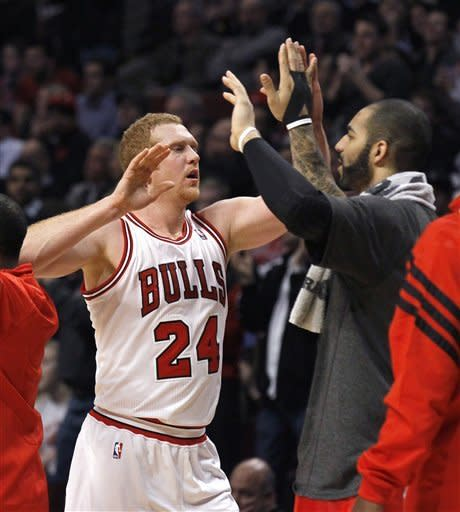 Chicago Bulls forward Brian Scalabrine (24) celebrates with forward Carlos Boozer during a break in the second quarter of an NBA basketball game against the New Jersey Nets on Monday, Jan. 23, 2012, in Chicago. (AP Photo/Charles Rex Arbogast)