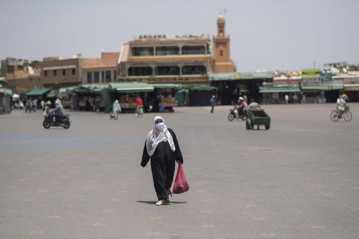 A woman walks with a grocery bag in the usually bustling landmark of Jemma el-Fnaa, in Marrakech, Morocco, Wednesday, July 22, 2020. Morocco's restrictions to counter the coronavirus pandemic have taken a toll on the carriage horses in the tourist mecca of Marrakech. (AP Photo/Mosa'ab Elshamy)