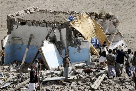 People gather on the wreckage of a house destroyed by an air strike in the Bait Rejal village west of Yemen's capital Sanaa April 7, 2015. REUTERS/Khaled Abdullah