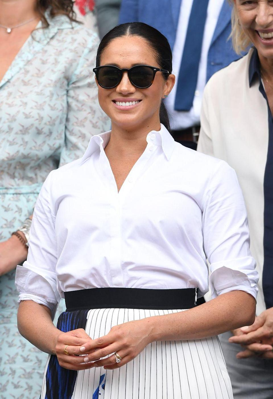 """<p>We earn a commission for products purchased through some links in this article.</p><p>The Duchess of Sussex joined Kate Middleton to watch Serena Williams and Simona Halep from the Royal Box. She wore a white shirt and plisse midi skirt from Hugo Boss for the outing, accessorised with the Bandwagon sunglasses from Le Specs.</p><p><a class=""""link rapid-noclick-resp"""" href=""""https://go.redirectingat.com?id=127X1599956&url=https%3A%2F%2Fwww.hugoboss.com%2Fuk%2Fa-line-skirt-in-portuguese-plisse-fabric-with-overprinted-motif%2Fhbeu50411310_965.html&sref=https%3A%2F%2Fwww.elle.com%2Fuk%2Ffashion%2Fcelebrity-style%2Fg28258118%2Fwimbledon-best-dressed-celebrities%2F"""" rel=""""nofollow noopener"""" target=""""_blank"""" data-ylk=""""slk:Shop Now"""">Shop Now</a> Hugo Boss A-line skirt in Portuguese plissé fabric</p>"""