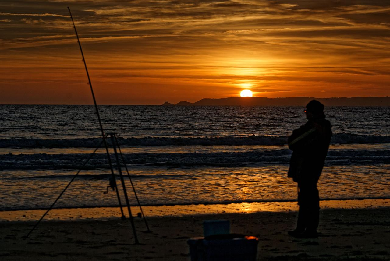 <p>The sun setting over Mumbles Head near Swansea, while a man is fishing in the nearby beach of Aberavon in south Wales. (Rex) </p>
