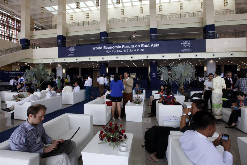 Participants sit at the entrance to Myanmar International Convention Center where the three-day World Economic Forum for East Asia is held in Naypyitaw, Myanmar, Wednesday, June 5, 2013. (AP Photo/Khin Maung Win)