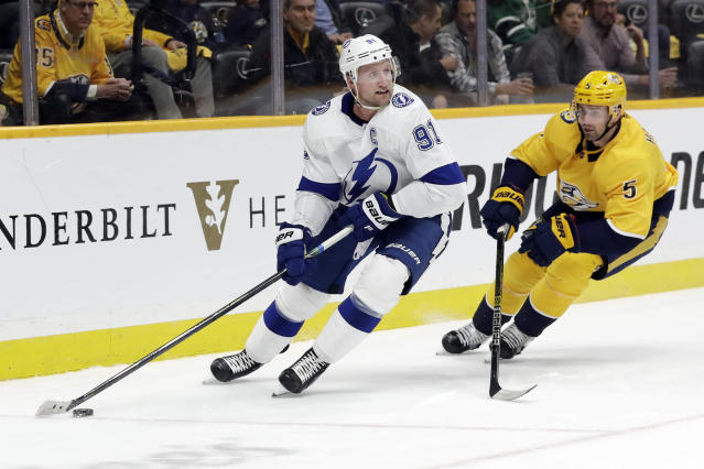 Tampa Bay Lightning center Steven Stamkos (91) is followed by Nashville Predators defenseman Dan Hamhuis (5) in the first period of an NHL hockey game Tuesday, Dec. 3, 2019, in Nashville, Tenn. (AP Photo/Mark Humphrey)