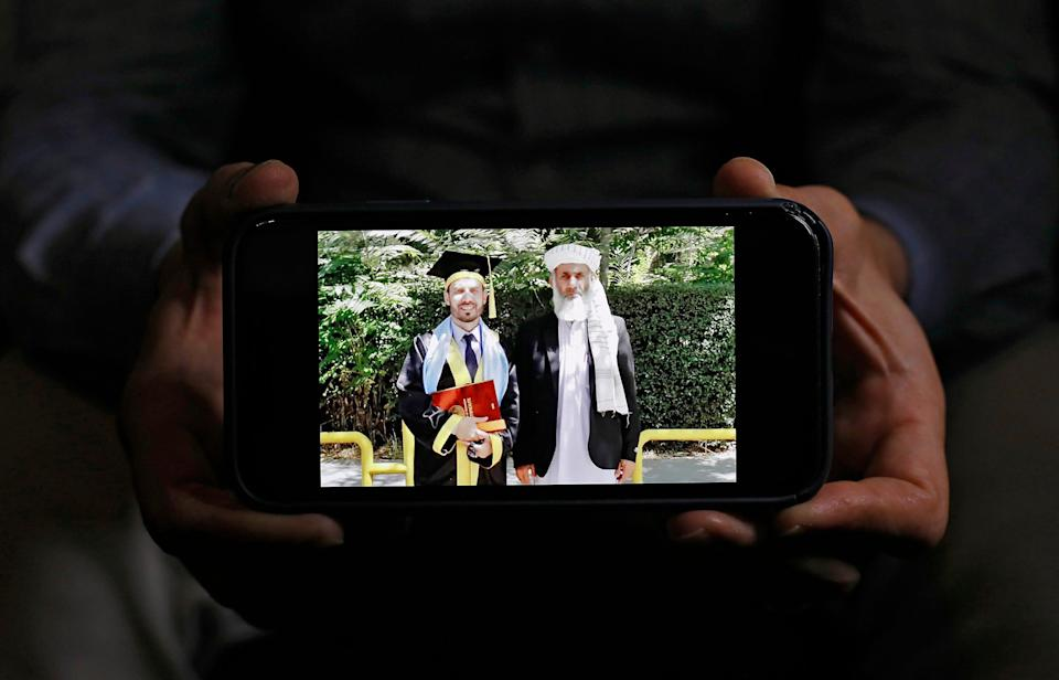 Shamsurahman Zaland shows off a photo with his father after sneaking back into Afghanistan to defend his master in Finance during 2019. Zaland, a refugee from Afghanistan, came here in 2018 with a Special Immigrant Visa for his work with the U.S. government.