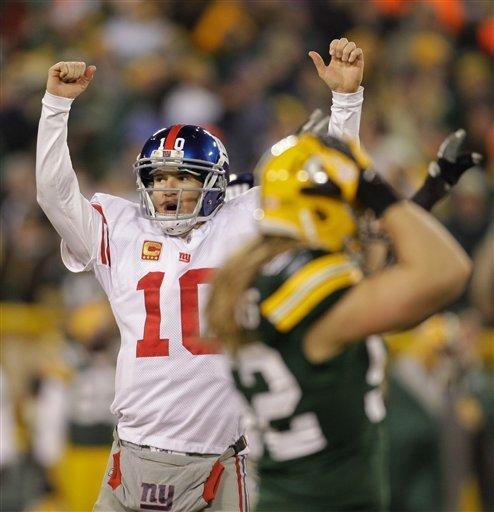 New York Giants quarterback Eli Manning reacts in front of Green Bay Packers linebacker Clay Matthews, right, after throwing a 37-yard touchdown pass to Hakeem Nicks during the first the first half of an NFL divisional playoff football game Sunday, Jan. 15, 2012, in Green Bay, Wis. (AP Photo/Darron Cummings)