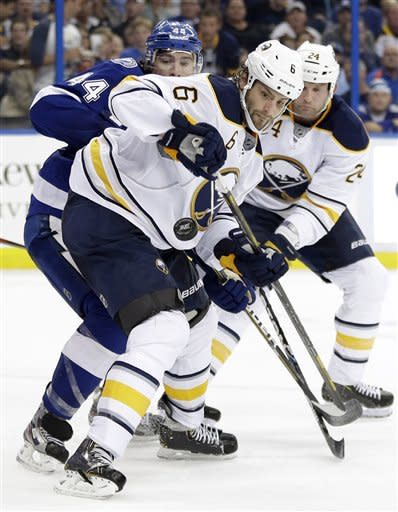 Buffalo Sabres defenseman Mike Weber (6) keeps the puck from Tampa Bay Lightning center Nate Thompson during the second period of an NHL hockey game Tuesday, Feb. 26, 2013, in Tampa, Fla. Defending on the play for the Sabres is Robyn Regehr, of Brazil (24). (AP Photo/Chris O'Meara)
