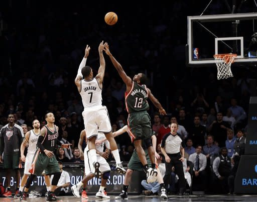 Brooklyn Nets guard Joe Johnson (7) scores over Milwaukee Bucks forward Luc Richard Mbah a Moute (12) with time expiring for a 113-11 overtime victory in their NBA basketball game at Barclays Center, Tuesday, Feb. 19, 2013 in New York. (AP Photo/Kathy Willens)