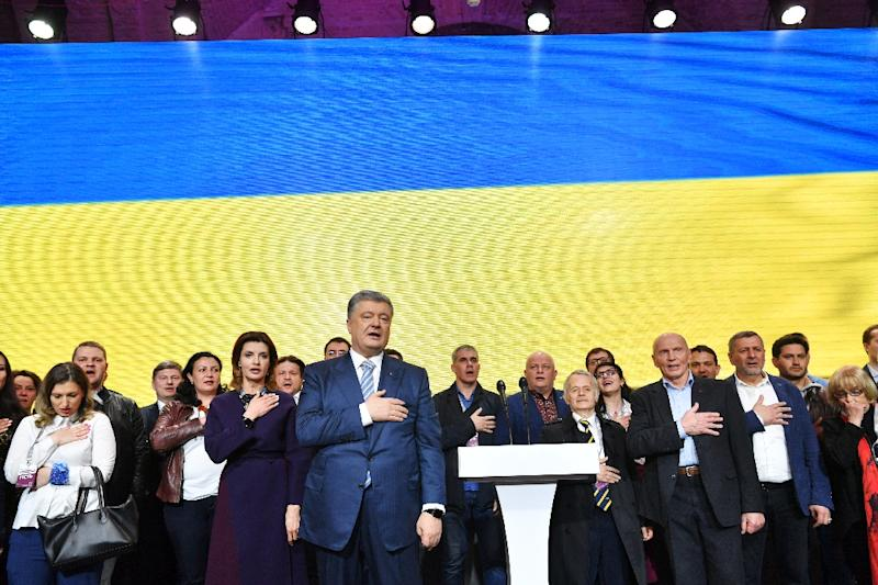 Outgoing Ukrainian President Petro Poroshenko (C) conceded defeat shortly after polls closed (AFP Photo/Sergei SUPINSKY)