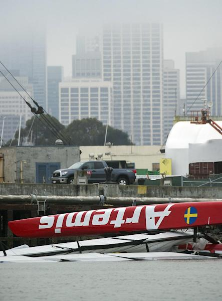 "Artemis Racing's 72-foot-long catamaran floats upside down at a Treasure Island dock on Friday, May 10, 2013, in San Francisco. Sailor Andrew ""Bart"" Simpson died the day before when the high-tech catamaran capsized during America's Cup training trapping him underwater. San Francisco's financial district is in the background, (AP Photo/Noah Berger)"