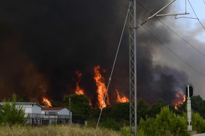 Flames burn near the buildings and railway lines in Tatoi area, northern Athens, Greece, Tuesday, Aug. 3, 2021. Greece Tuesday grappled with the worst heatwave in decades that strained the national power supply and fueled wildfires near Athens and elsewhere in southern Greece. As the heat wave scorching the eastern Mediterranean intensified, temperatures reached 42 degrees Celsius (107.6 Fahrenheit) in parts of the Greek capital. (AP Photo/Michael Varaklas)