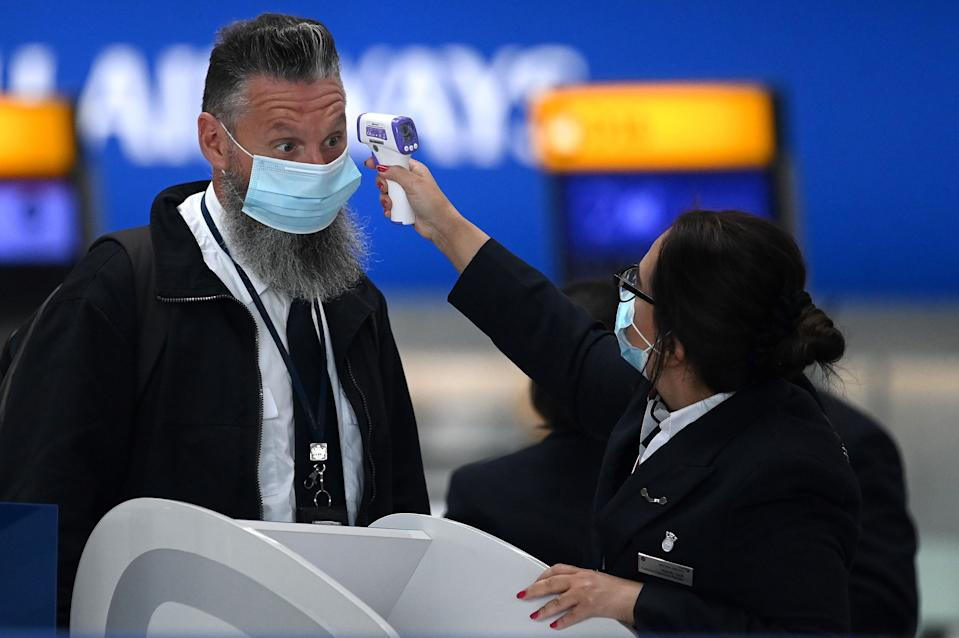 Passengers wearing face masks or covering due to the COVID-19 pandemic, have their temperature taken as they queue at a British Airways check-in desk at Heathrow airport, west London, on July 10, 2020. - The British government on Friday revealed the first exemptions from its coronavirus quarantine, with arrivals from Germany, France, Spain and Italy no longer required to self-isolate from July 10. Since June 8, it has required all overseas arrivals -- including UK residents -- to self-quarantine to avoid the risk of importing new cases from abroad. (Photo by DANIEL LEAL-OLIVAS / AFP) (Photo by DANIEL LEAL-OLIVAS/AFP via Getty Images)
