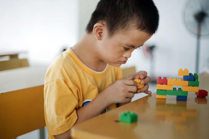 In this photo taken on Wednesday, Aug. 8, 2012, Le Trung Hong Phuc, 9, plays with colored blocks at a rehabilitation center in Danang, Vietnam. The children were born with physical and mental disabilities that the center's director says were caused by their parents' exposure to the chemical dioxin in the defoliant Agent Orange. On Thursday, the U.S. for the first time will begin cleaning up leftover dioxin that was stored at the former military base that's now part of Danang's airport. (AP Photo/Maika Elan)