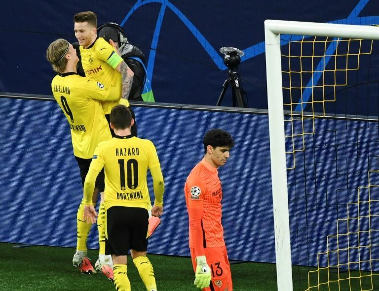 Erling Braut Haaland (L) lifts Marco Reus off his feet in celebrating scoring against Sevilla in the last 16 of the Champions League