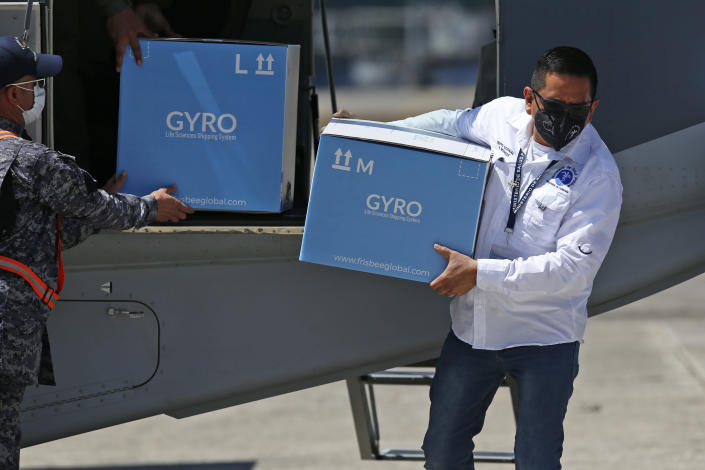 Workers unload boxes of Moderna COVID-19 vaccines and supplies donated by Israel at an Air Force base in Guatemala City, Thursday, Feb. 25, 2021. (AP Photo/Moises Castillo)