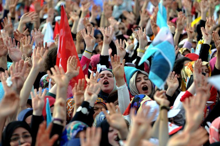 Supporters of the Turkish Prime Minister and Presidential candidate make the four fingers' sign during a rally on August 3, 2014 in Istanbul