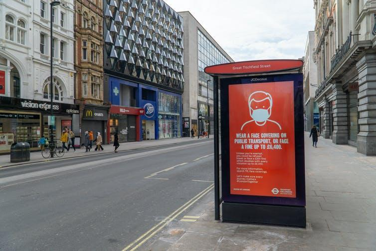An empty London street during lockdown, with a COVID warning poster on a bus stop