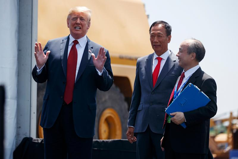 President Donald Trump talks to reporters while standing with Foxconn chairman Terry Gou, center, and CEO of SoftBank, Masayoshi Son, during a groundbreaking event, Thursday, June 28, 2018, in Mt. Pleasant, Wis. (AP Photo/Evan Vucci)