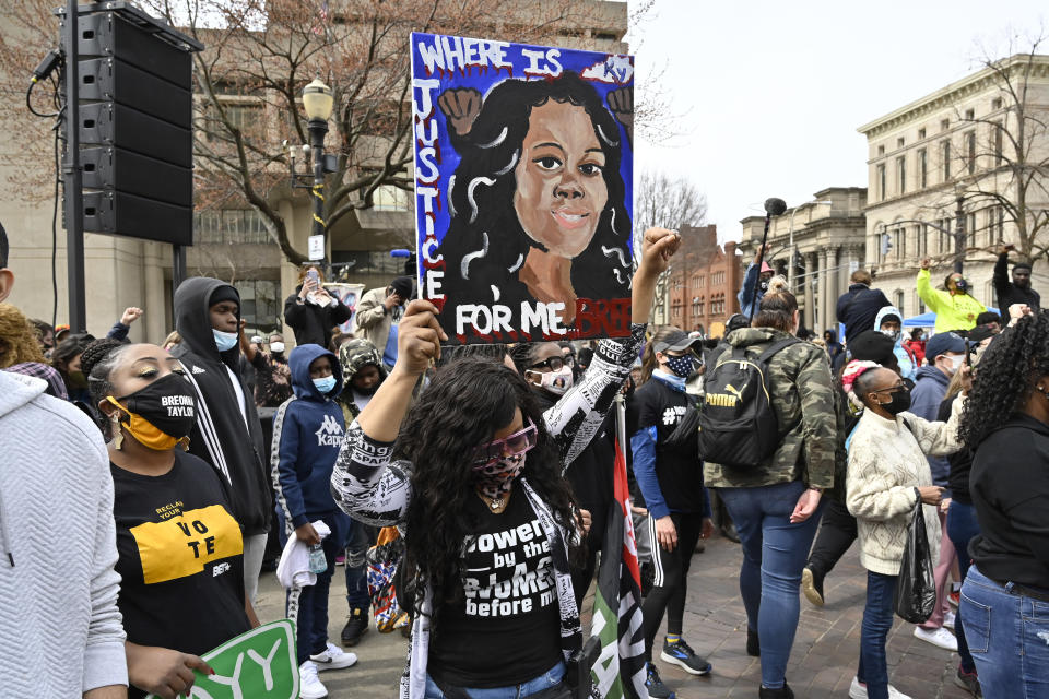 FILE - In this March 13, 2021 file photo, a protester holds up a painting of Breonna Taylor during a rally on the one year anniversary of her death at Jefferson Square Park in Louisville, Ky. On Friday, April 9, 2021, Gov. Andy Beshear has signed a partial ban on no-knock warrants a year after the fatal shooting of Taylor. (AP Photo/Timothy D. Easley)