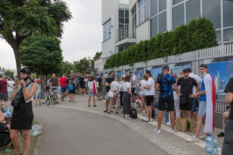 People queue outside the Belarusian embassy to cast their votes during the presidential election in Warsaw